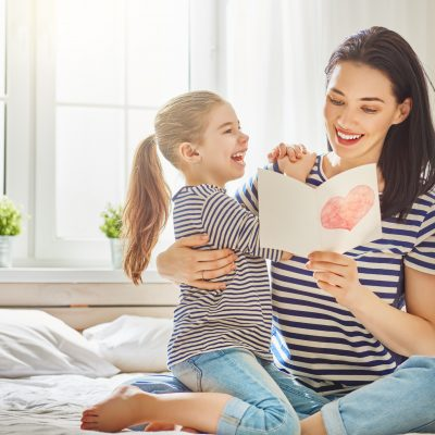 mother with daughter reading mother's day card
